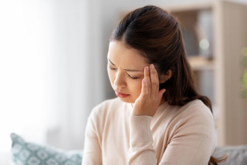 people and health problem concept - sick asian woman having headache at home